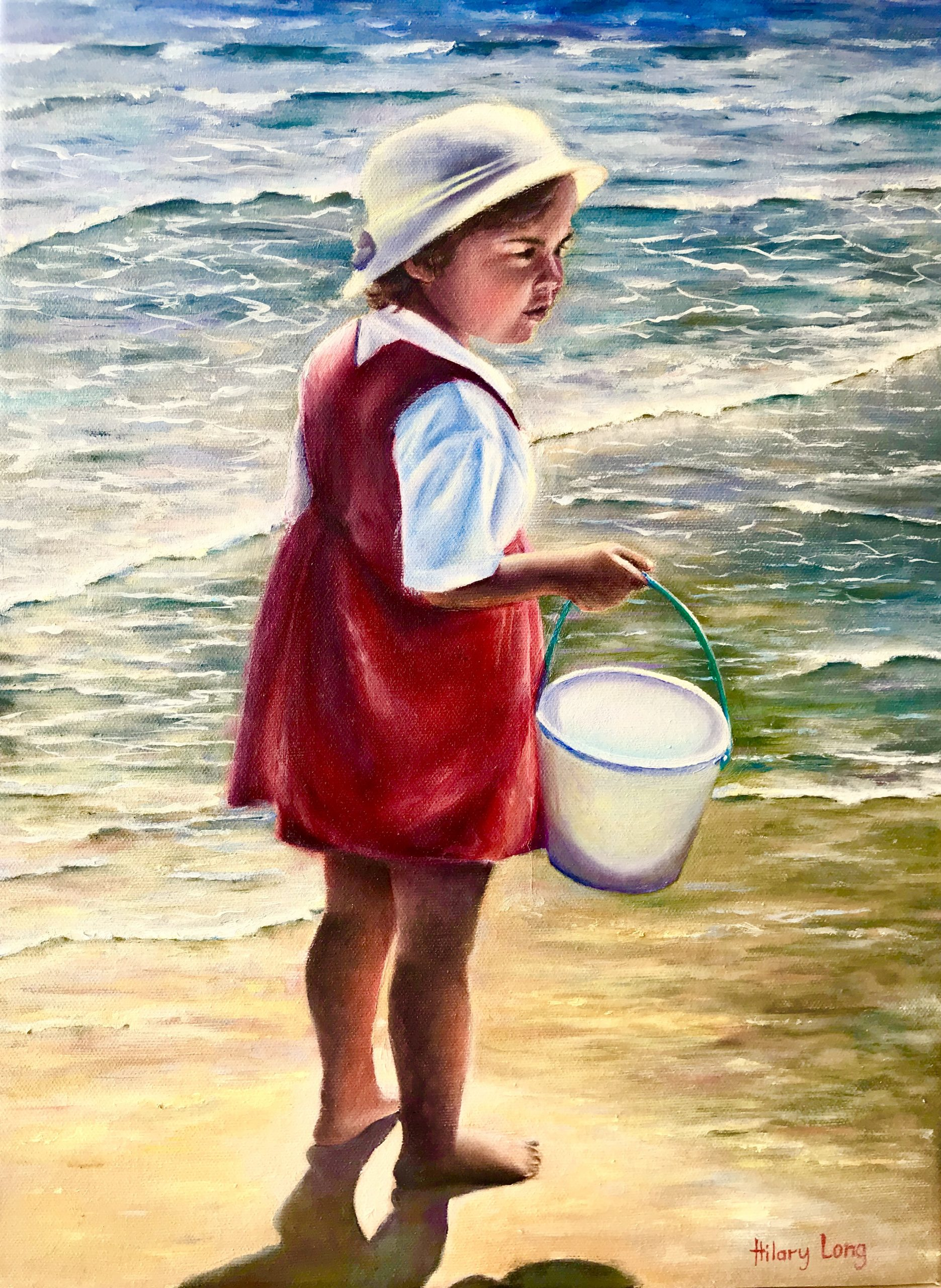 Girl with bucket by the sea shore